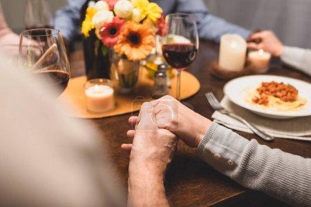 Photo pour Crochet vue d'un homme tenant la main d'un ami et priant pendant le dîner - image libre de droit