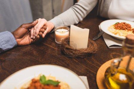 Photo pour Crochet vue d'un Africain américain tenant la main d'un ami et priant pendant le dîner - image libre de droit