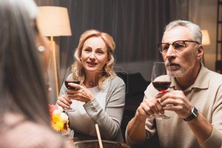 enfoque selectivo de la mujer sonriente y el hombre hablando con un amigo durante la cena