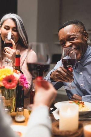 Photo pour L'accent sélectif d'une femme asiatique souriante et d'un homme américain africain tenant des verres à vin pendant le dîner - image libre de droit