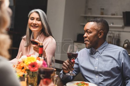 selective focus of smiling asian woman and african american man holding wine glasses during dinner