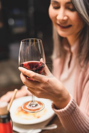 Photo for Selective focus of smiling asian woman holding wine glass during dinner - Royalty Free Image