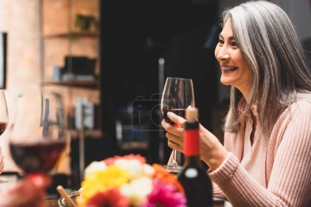 selective focus of smiling asian woman holding wine glass during dinner