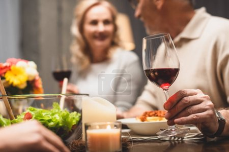 Photo for Selective focus of man holding wine glass and talking with smiling woman during dinner - Royalty Free Image