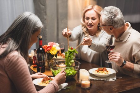 Photo for Smiling woman taking salad from bowl and talking with friend during dinner - Royalty Free Image