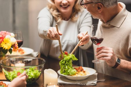 cropped view of smiling woman putting salad on plate of friend during dinner