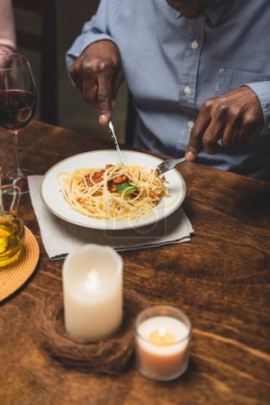 Photo for Cropped view of african american man eating pasta during dinner - Royalty Free Image