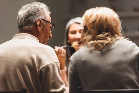 Photo pour Vue arrière de l'homme et la femme parler avec sourire asiatique ami pendant le dîner - image libre de droit