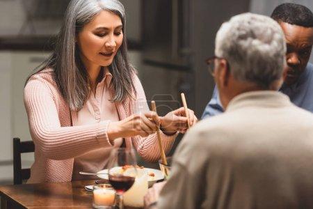 Photo pour Foyer sélectif d'amis multiculturels parlant pendant le dîner - image libre de droit