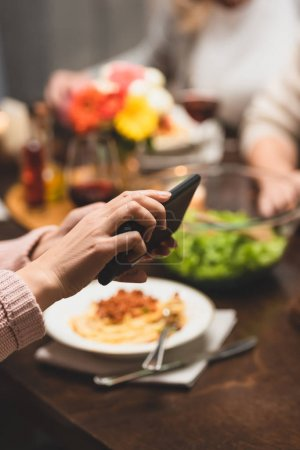 Photo for Cropped view of woman holding smartphone during dinner - Royalty Free Image