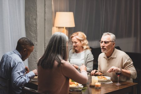 Photo for Selective focus of smiling man and woman talking with multicultural friends and eating during dinner - Royalty Free Image
