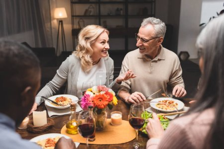 Photo for Selective focus of smiling man and woman talking with multicultural friends during dinner - Royalty Free Image