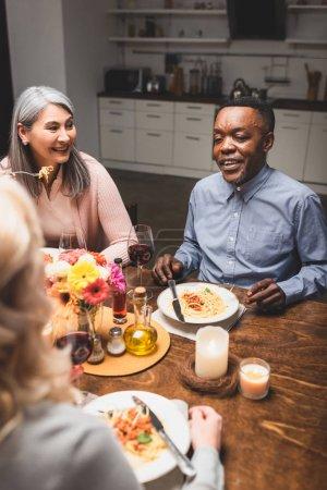 Selektiver Fokus multikultureller Männer und Frauen im Gespräch mit Freunden beim Abendessen