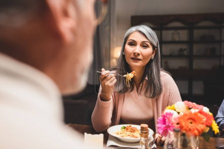 Photo for Selective focus of asain woman eating pasta and looking at friend during dinner - Royalty Free Image