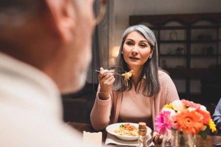 Foto de Enfoque selectivo de asain mujer comiendo pasta y mirando a amigo durante la cena - Imagen libre de derechos