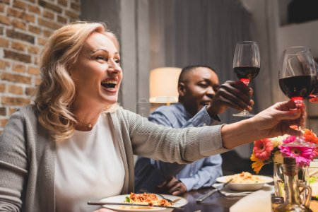 selective focus of smiling multicultural friends clinking during dinner