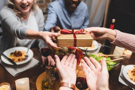 Photo pour Vue recadrée de l'homme et de la femme multiculturels donnant cadeau à des amis pendant le dîner - image libre de droit