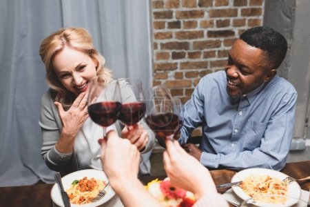 Photo for Cropped view of friends clinking with caucasian woman and african american man during dinner - Royalty Free Image