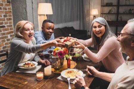 Foto de Sonrientes amigos multiculturales sosteniendo regalo y mirando al hombre durante la cena - Imagen libre de derechos