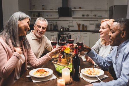 Photo for Smiling multicultural friends clinking with wine glasses during dinner - Royalty Free Image