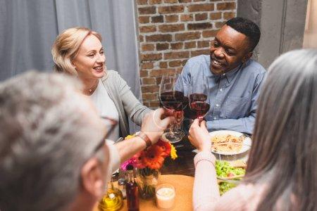 Photo pour Vue recadrée de femme et d'homme cliquetant avec des amis multiculturels souriants pendant le dîner - image libre de droit