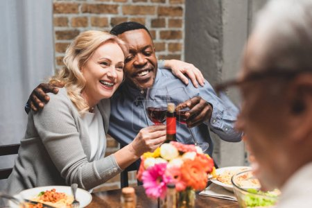 Photo for Selective focus of smiling multicultural friends hugging and clinking during dinner - Royalty Free Image