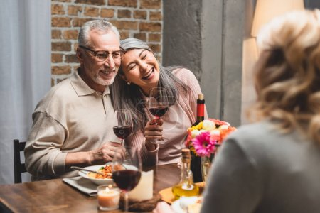 Photo for Selective focus of smiling multicultural friends holding wine glasses during dinner - Royalty Free Image