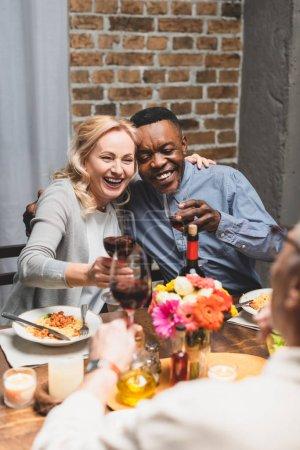 Photo pour Orientation sélective des amis multiculturels souriants serrer la tête et claquer la tête pendant le souper - image libre de droit