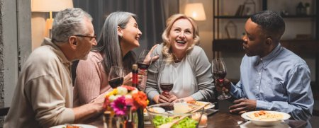 Photo for Panoramic shot of smiling multicultural friends talking and holding wine glasses during dinner - Royalty Free Image