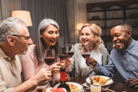smiling multicultural friends talking and clinking with wine glasses during dinner
