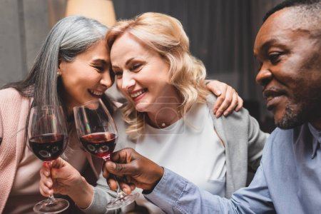 Photo for Smiling multicultural friends hugging and clinking with wine glasses during dinner - Royalty Free Image