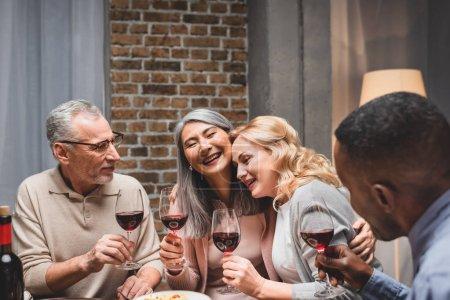 Photo pour Des amis multiculturels souriants serrant et tenant des verres à vin pendant le dîner - image libre de droit