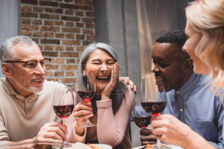 Photo for Smiling multicultural friends hugging and holding wine glasses during dinner - Royalty Free Image