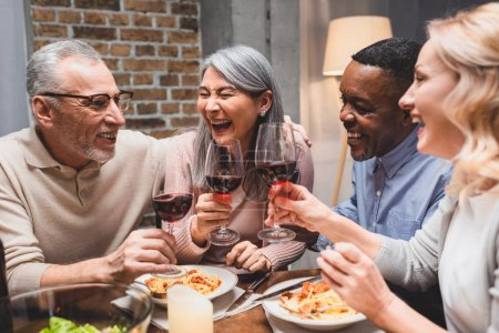 Photo for Smiling multicultural friends talking and clinking with wine glasses during dinner - Royalty Free Image
