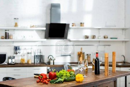 Photo pour Légumes. bouteilles avec vin et bière, verres à vin, bol, Moulin à poivre, moulin à sel sur table en bois dans la cuisine - image libre de droit