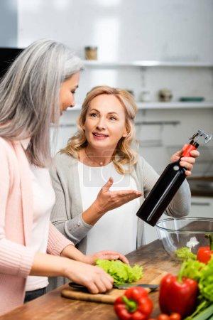 Foto de Sonriente mujer apuntando con la mano a la botella con sacacorchos y mirando a un amigo - Imagen libre de derechos