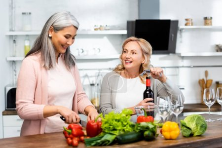 Photo for Smiling woman opening wine bottle with corkscrew and looking at her asian friend with knife - Royalty Free Image