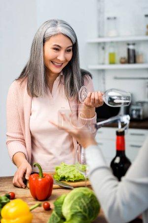 Foto de Enfoque selectivo de sonriente mujer asiática sosteniendo copa de vino y mirando a su amigo - Imagen libre de derechos