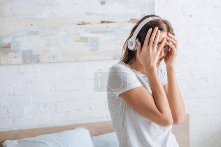 Photo pour Femme gaie couvrant visage tout en souriant et en écoutant de la musique à la maison - image libre de droit