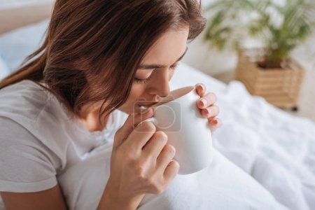 Photo pour Attrayant jeune femme boire du thé dans la chambre - image libre de droit