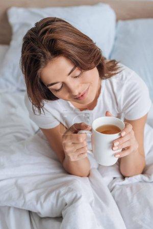 Photo pour Vue aérienne de fille heureuse avec les yeux fermés tenant tasse avec thé au lit - image libre de droit