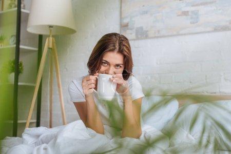 Photo pour Foyer sélectif de la jeune femme regardant la caméra tout en tenant la tasse avec du thé au lit - image libre de droit