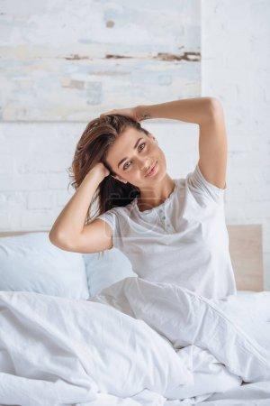 Photo pour Femme heureuse touchant les cheveux et regardant la caméra au lit - image libre de droit
