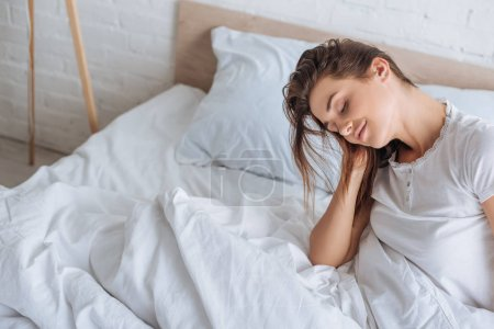 Photo for Dreamy woman with closed eyes resting in bed - Royalty Free Image