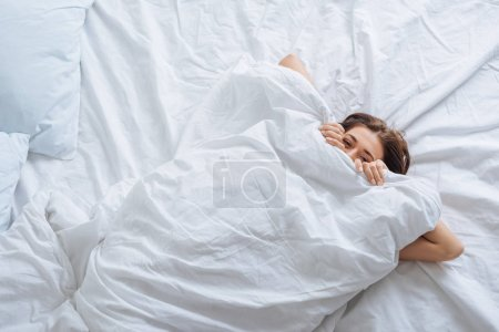 Photo for Top view of young woman covering face with blanket while resting in bed - Royalty Free Image
