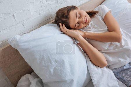 Foto de Mujer joven sonriente que se relaja mientras se acuesta en la cama - Imagen libre de derechos