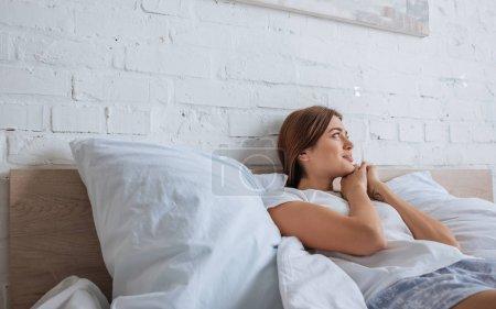 Photo pour Une jeune femme souriante rêvant allongée sur son lit - image libre de droit
