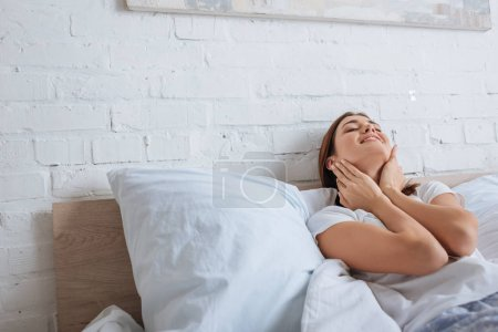 Foto de Mujer feliz tocando el cuello mientras sueña y miente en la cama - Imagen libre de derechos