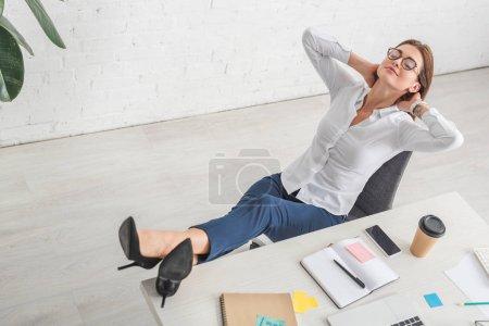 Photo pour Belle femme d'affaires dans des lunettes refroidissant dans le bureau - image libre de droit