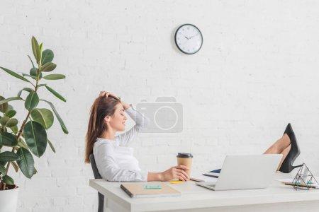 Photo pour Vue de côté de femme d'affaires heureuse refroidissant dans le bureau - image libre de droit